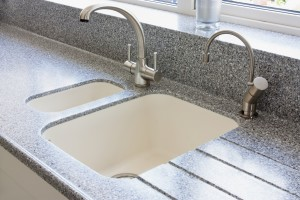 granite kitchen worktop and ceramic sunken sink with hot water tap and normal modern tap